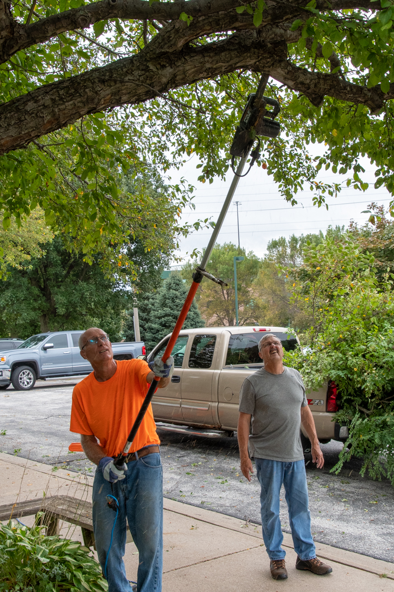 September 21, 2019:  Fall work day finds Tim Lambert and caretaker Denny Peters work on trimming branches over a doorway to the building.