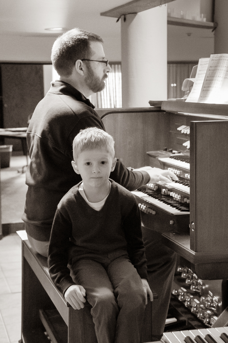 October 13, 2019:  With his young son Armin by his side, Dr. Chris Krampe, Director of Music, plays the organ for a Worship service.