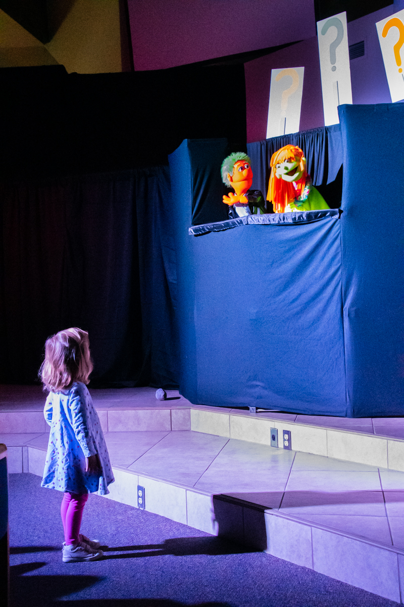 November 10, 2019:  Captivated by the puppets, a young girl wanders close for a better view during the ACE Puppet Troupe performance.