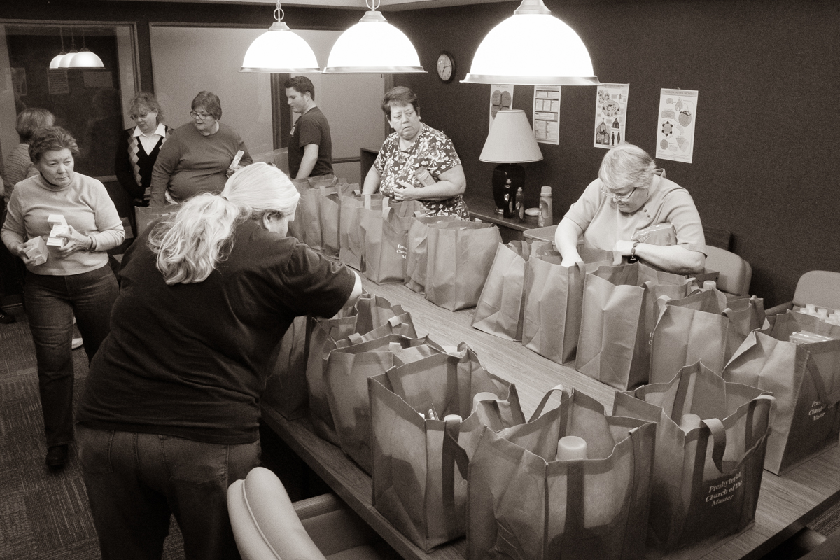 November 15, 2019: An assembly line of volunteers stuff bags with household items for donation as part of BART (Benson Area Refugee Taskforce).