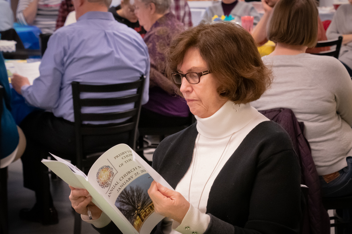 January 27, 2019:  The annual meeting of the congregation always draws interest. Sandie Hanna reads through the printed report before the start.