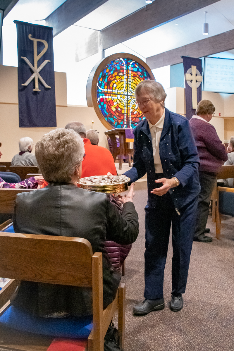 March 10, 2019:  Volunteer Mary McLean passes the Communion tray as a server of the Lord's Supper.