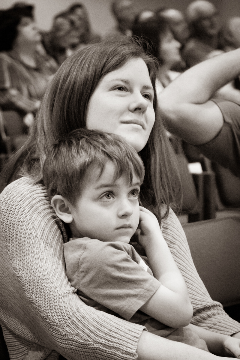 March 17, 2019:  Sitting with Katie, his mother, Max Petersen watches the video screens attentively during Worship service.