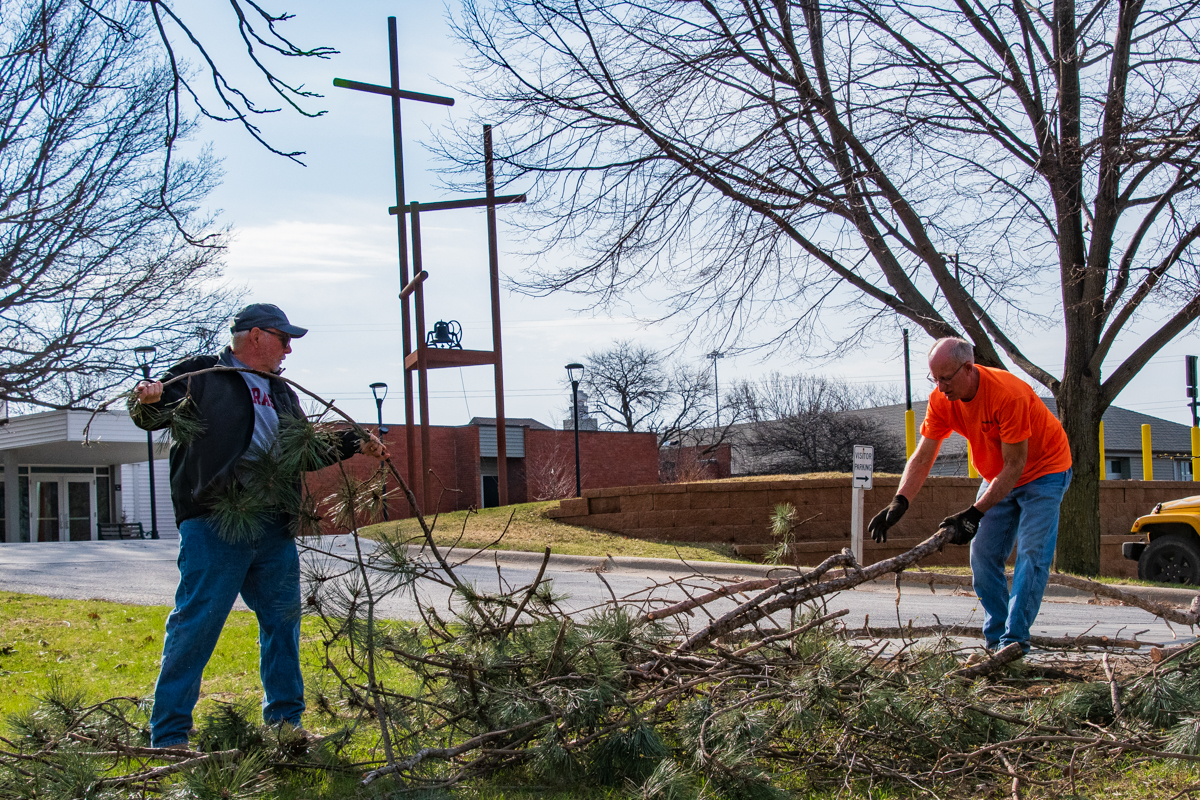 April 6, 2019:  Brad Denton and Tim Lambert work to trim trees and clean-up the branches during the annual Spring workday.