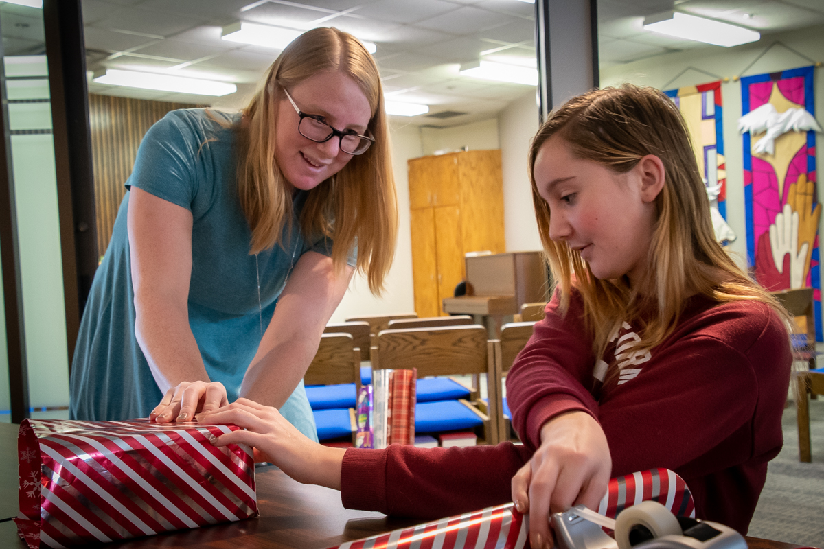December 2, 2018:  Erica Koslosky assists Maya Risling with Christmas gift wrapping as a fundraiser to support the 2019 Youth Triennium trip.